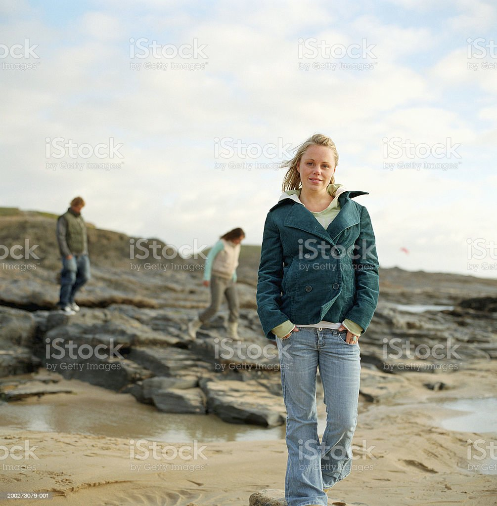 Young woman walking on beach, portrait, people on rocks in background stock photo
