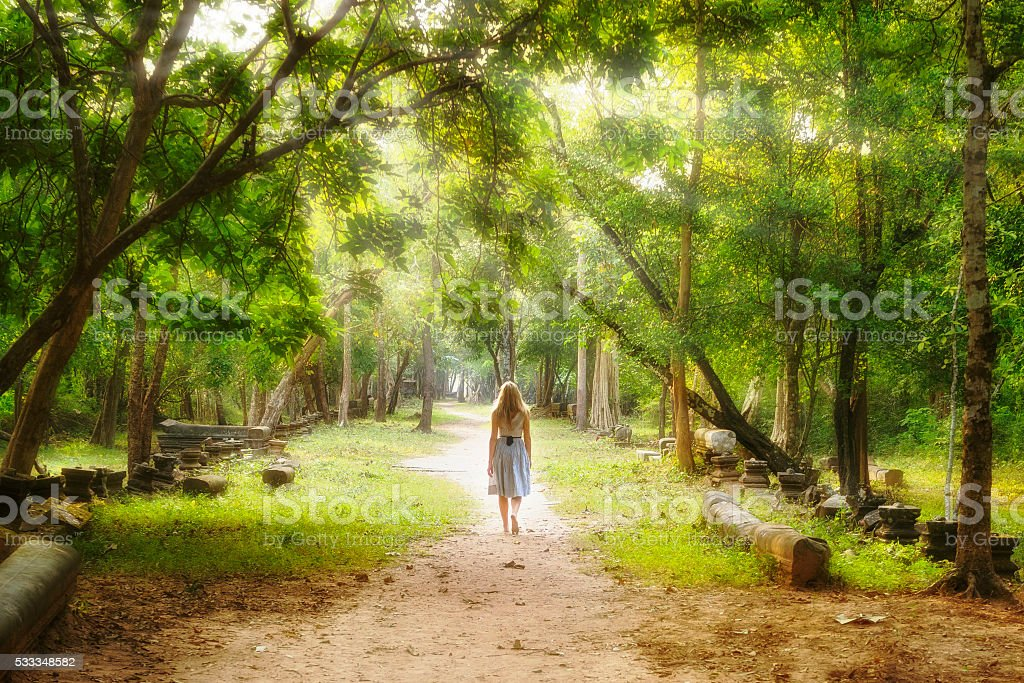Young woman walking on mysterious path into an enchanted forest.