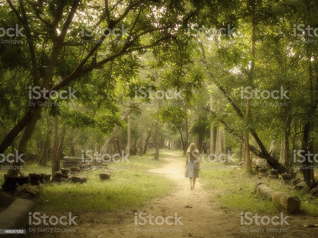 Young Woman Walking on Path into Enchanted Forest stock photo