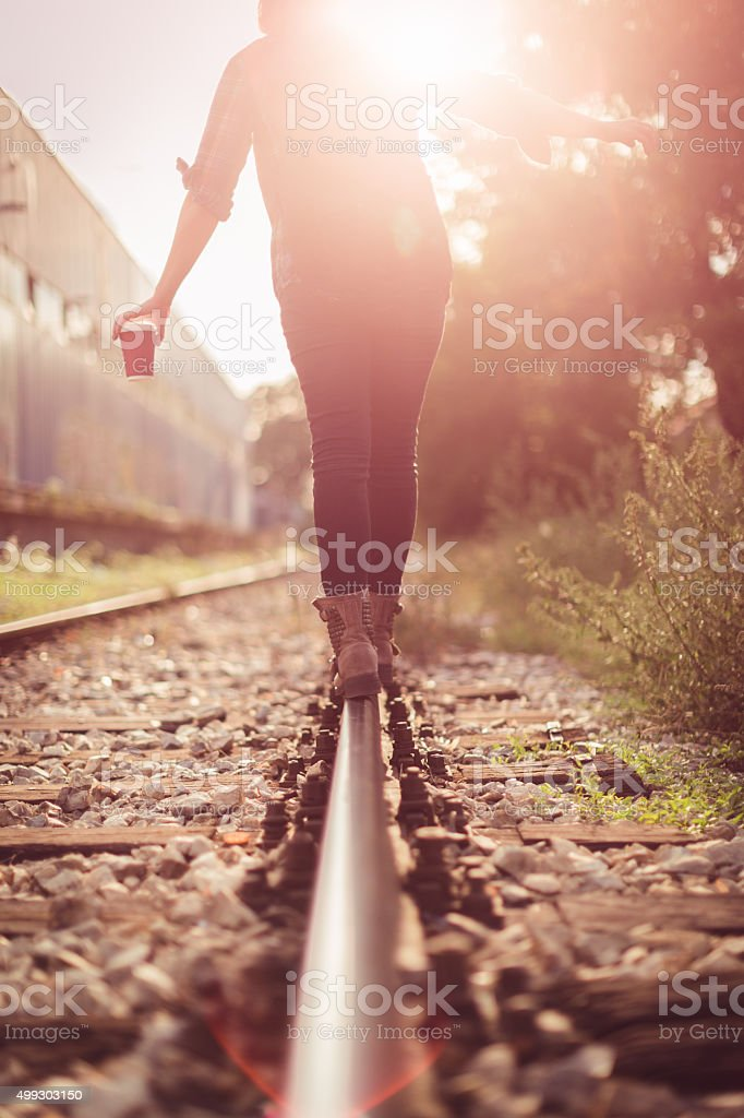 Young woman walking on railway tracks stock photo