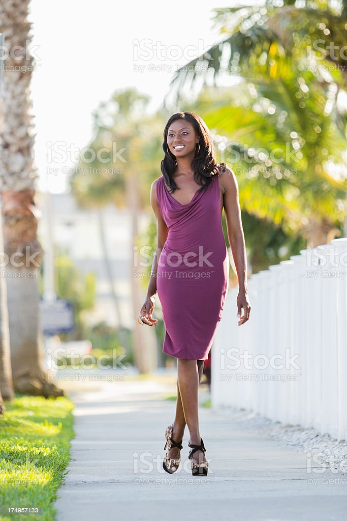 Young Woman Walking On Sidewalk stock photo