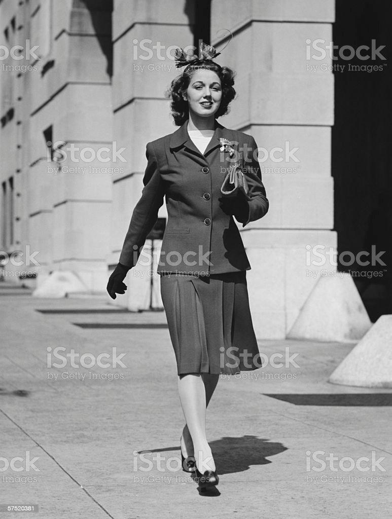 Young woman walking on sidewalk, (B&W) stock photo