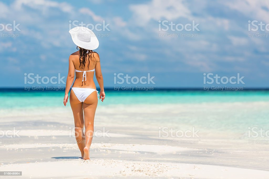 Young woman walking on the beach stock photo
