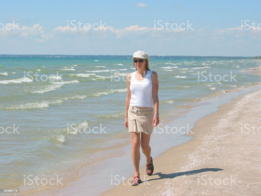 Young woman walking on the beach royalty-free stock photo