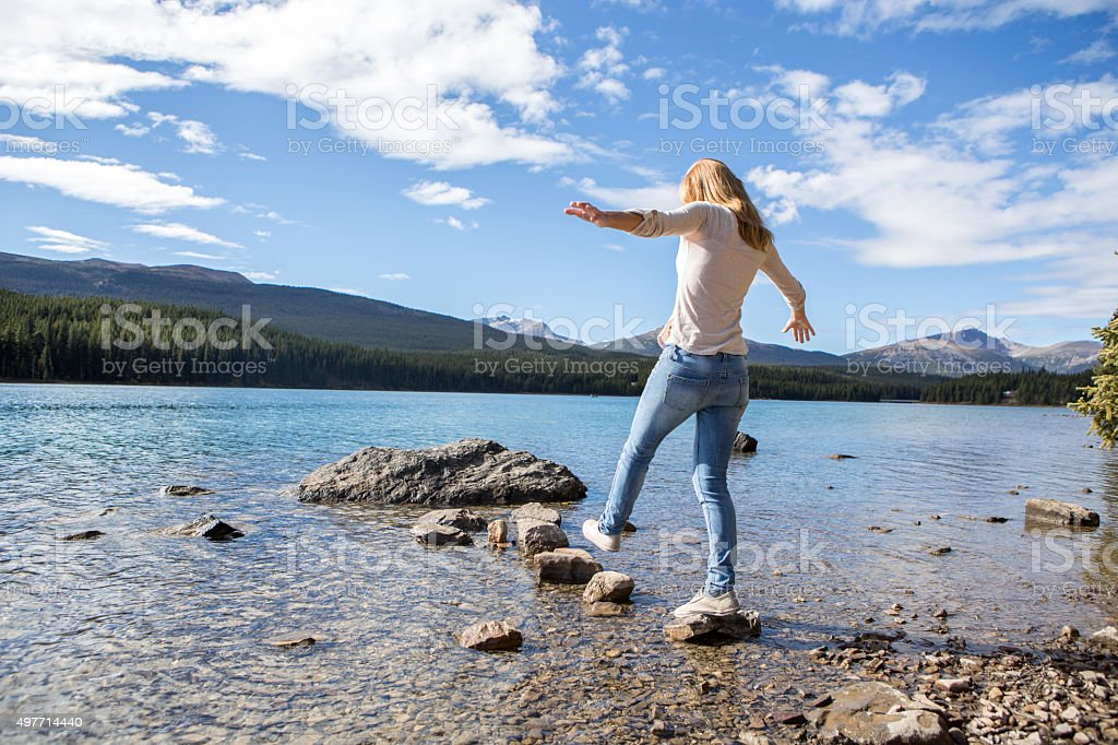 Young woman walking on the rocks above the water stock photo