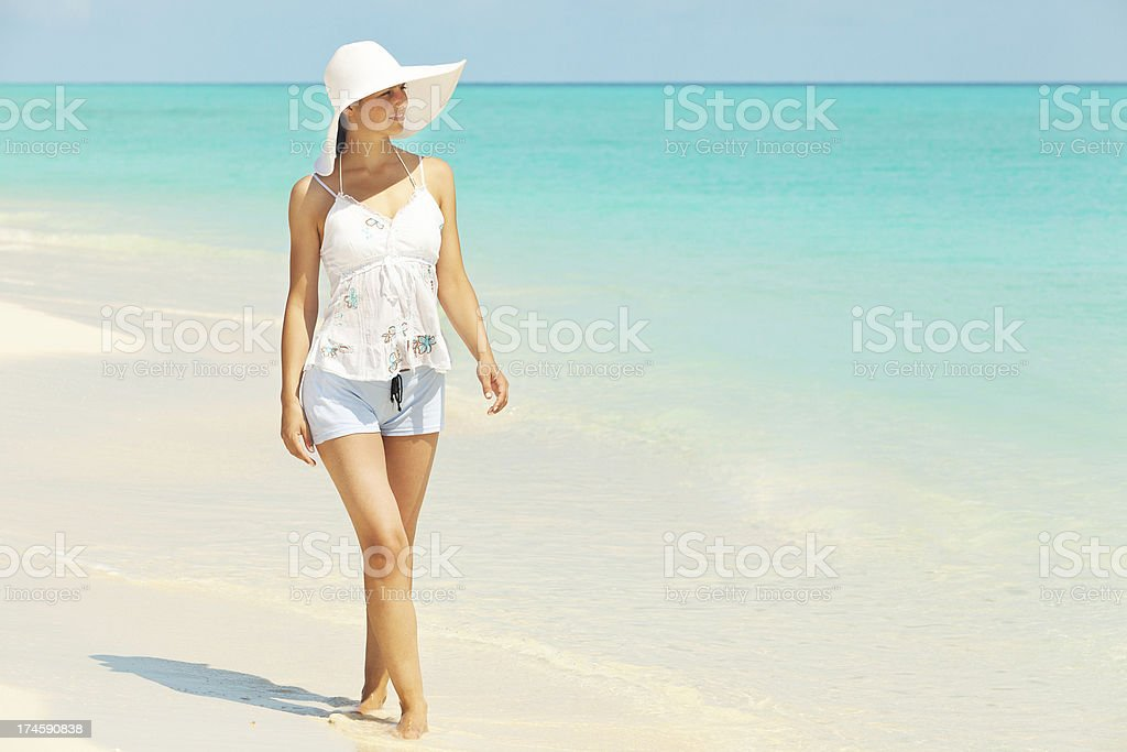Young woman walking on white sand beach stock photo