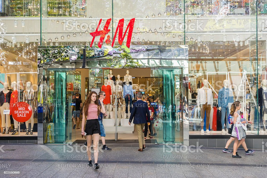 Young woman walking out of H&M store in Brisbane stock photo