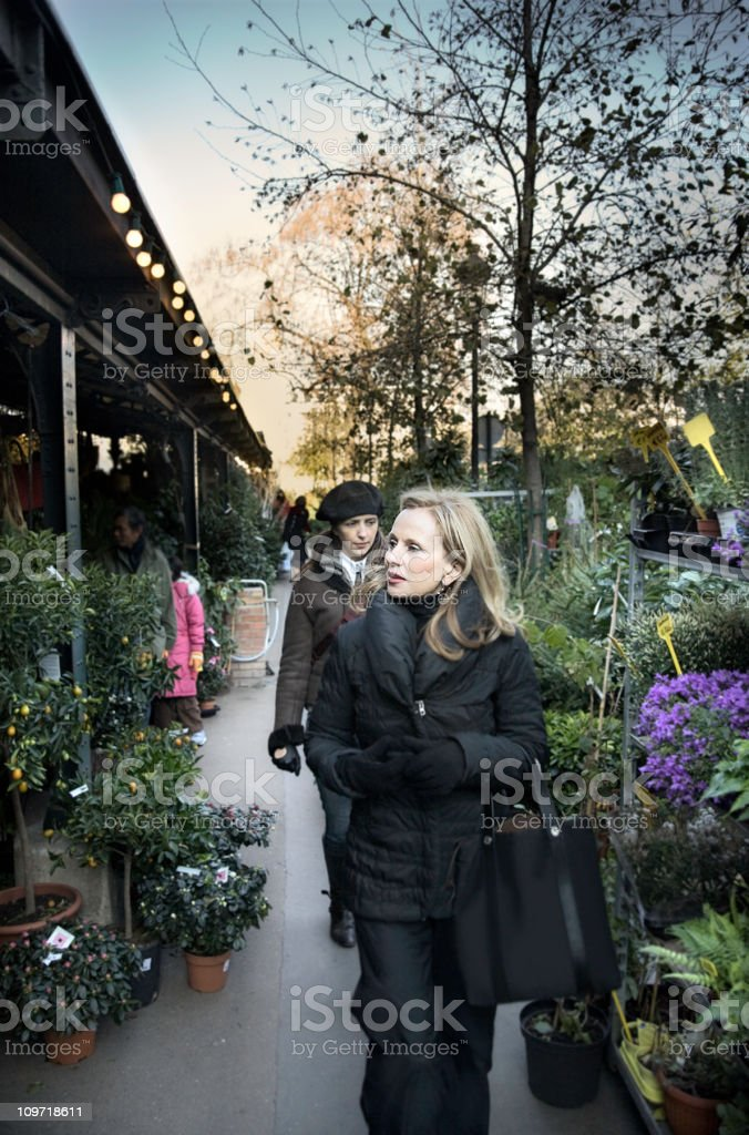 Young Woman Walking Through Flower Market on Cold Day royalty-free stock photo