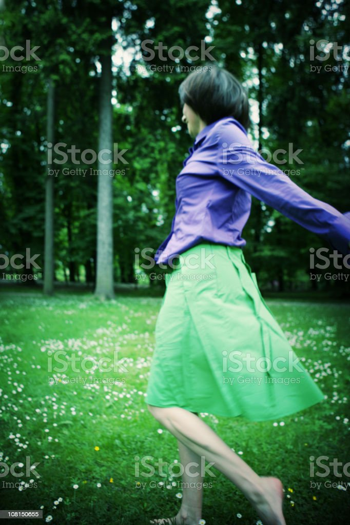 Young Woman Walking Through Grass in Park royalty-free stock photo