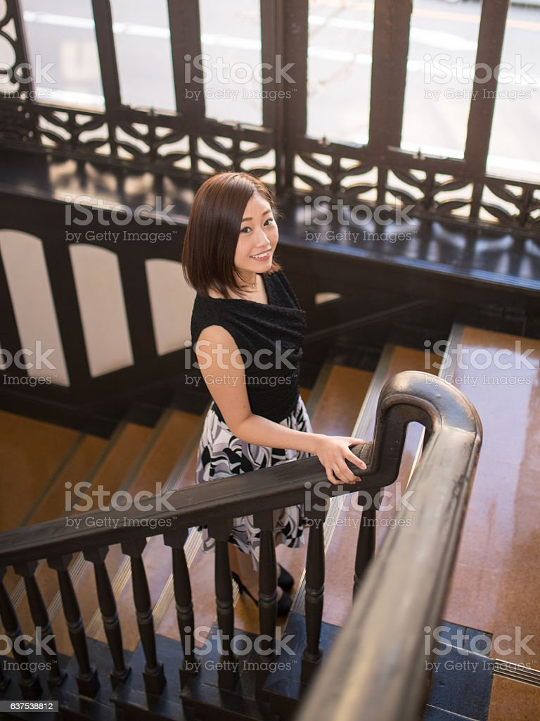 Young woman walking up stairs stock photo