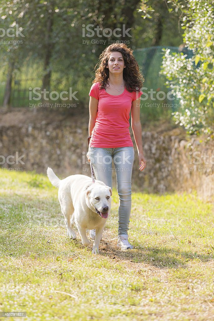 Young Woman Walking with Her Dog royalty-free stock photo