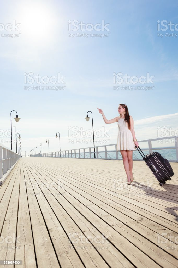 Young woman walking with suitcase on wheels stock photo