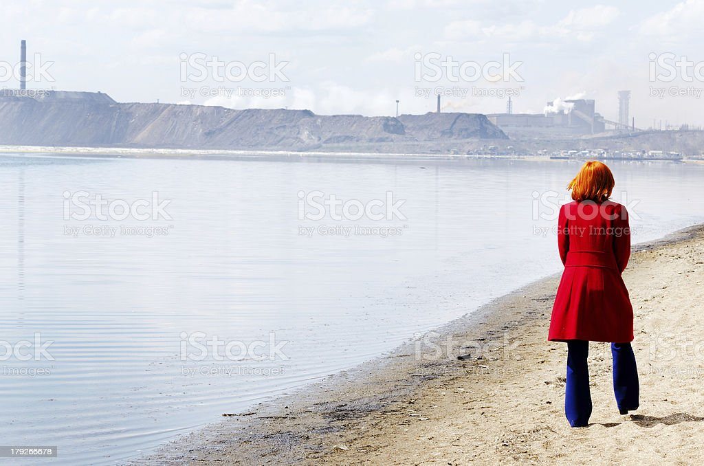 Young woman walks alone on a beach royalty-free stock photo