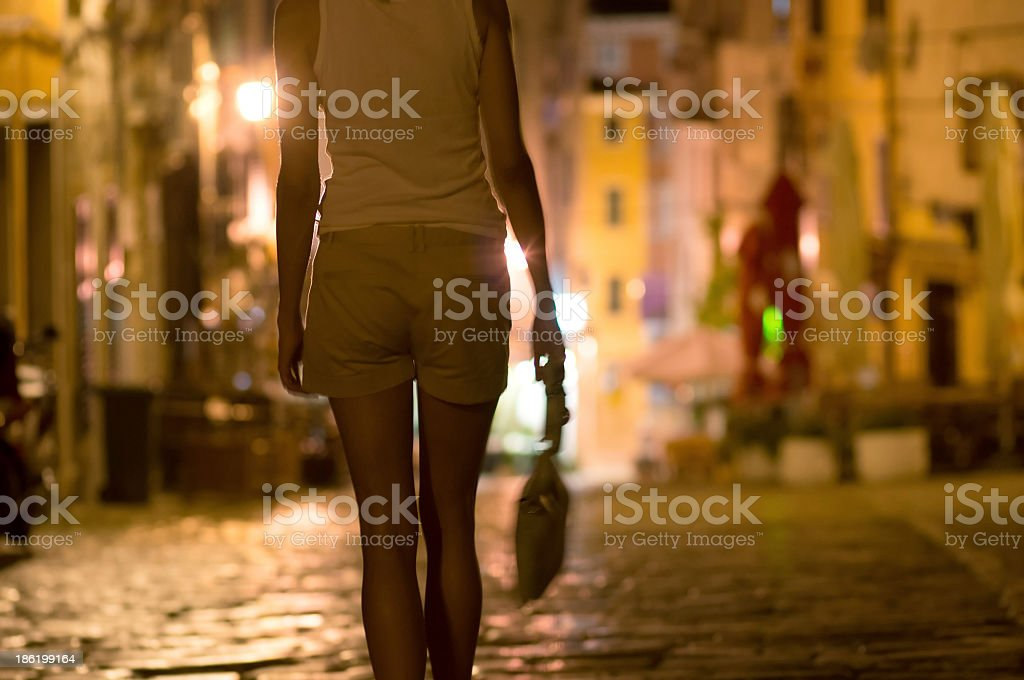 Young woman walks alone through a street at night stock photo