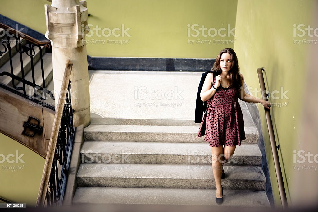 young woman walks downstairs royalty-free stock photo