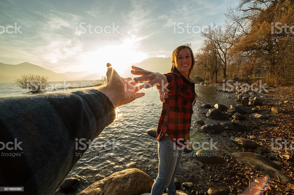 Young woman walks on lake shore holds a man's hand stock photo