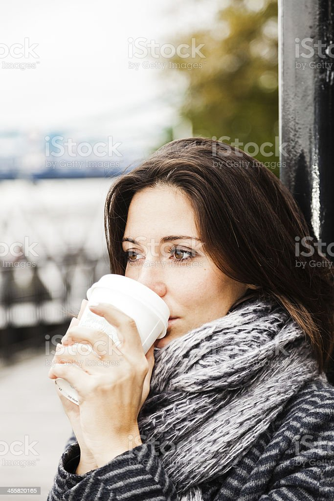 Young woman warms up drinking from a coffee cup stock photo