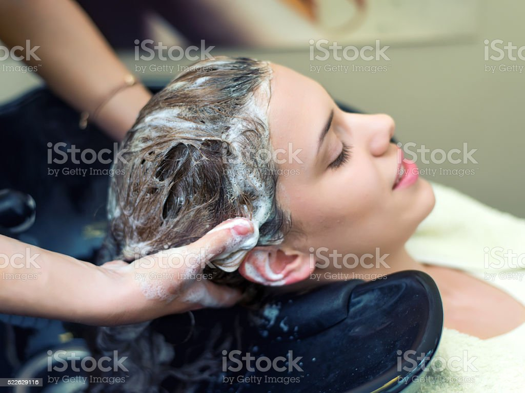 Young woman washing hair in salon stock photo
