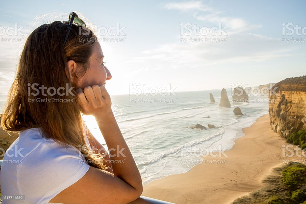 Young woman watches the sunset at the Twelve Apostles stock photo