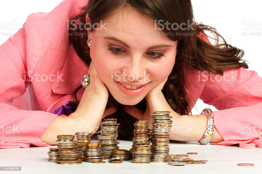 Young woman watching stacks of coins royalty-free stock photo