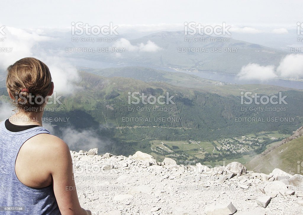 Young woman watching the Highlands mountains horizon in Scotland stock photo