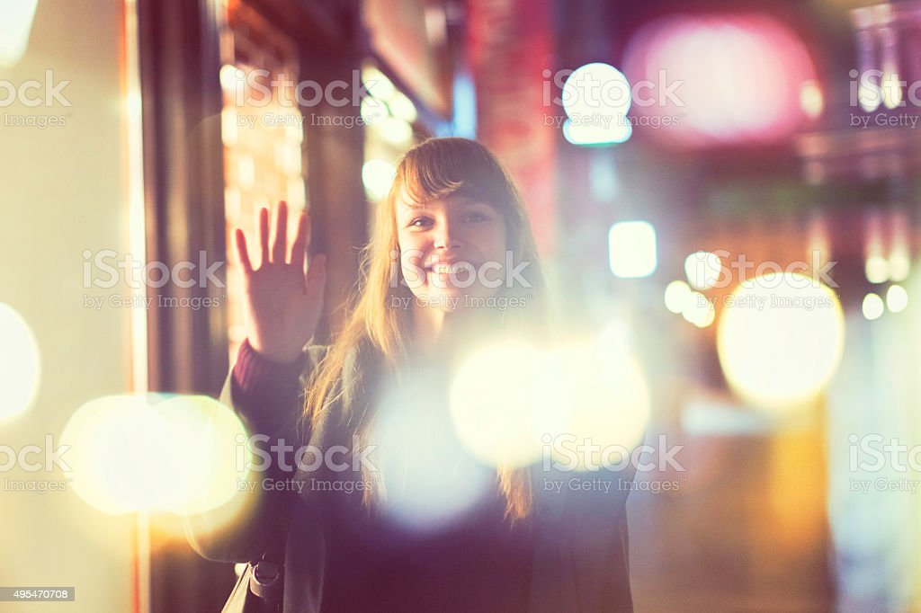 Young woman waving hand on the street stock photo
