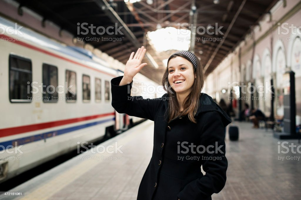 Young Woman Waving in A Train Station stock photo