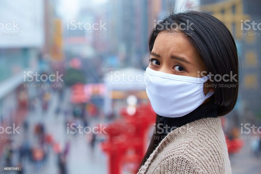 young woman wear mask in the foggy city stock photo