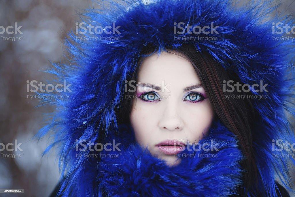 Young woman wearing a furry blue hood stock photo