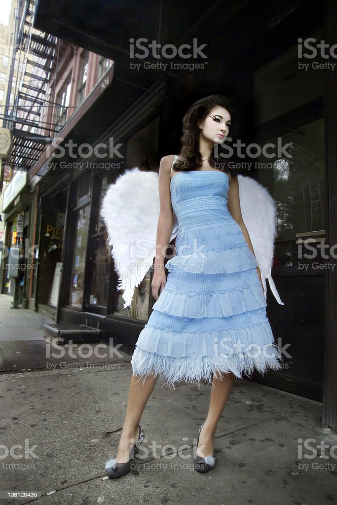 Young Woman Wearing Angel Wings on Urban Street royalty-free stock photo