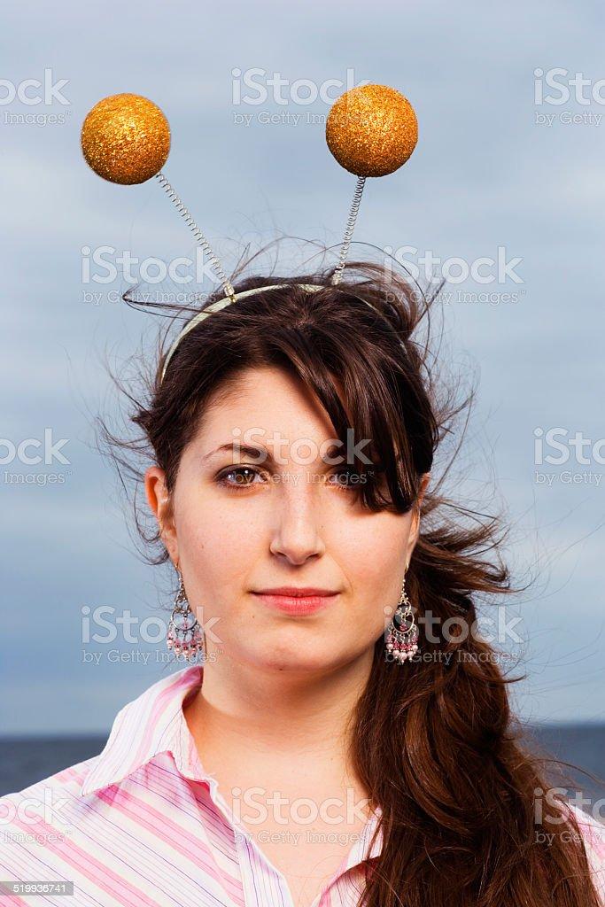 Young woman wearing antenna headband, portrait, close-up stock photo