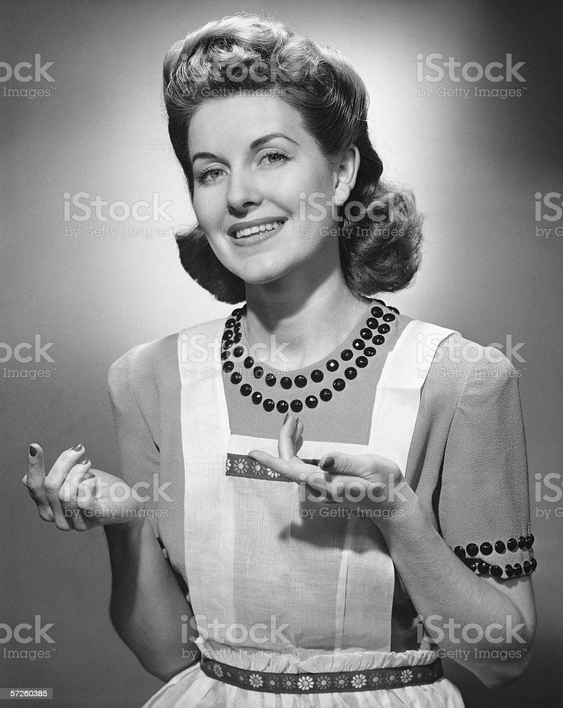 Young woman wearing apron, standing, smiling, (B&W) stock photo