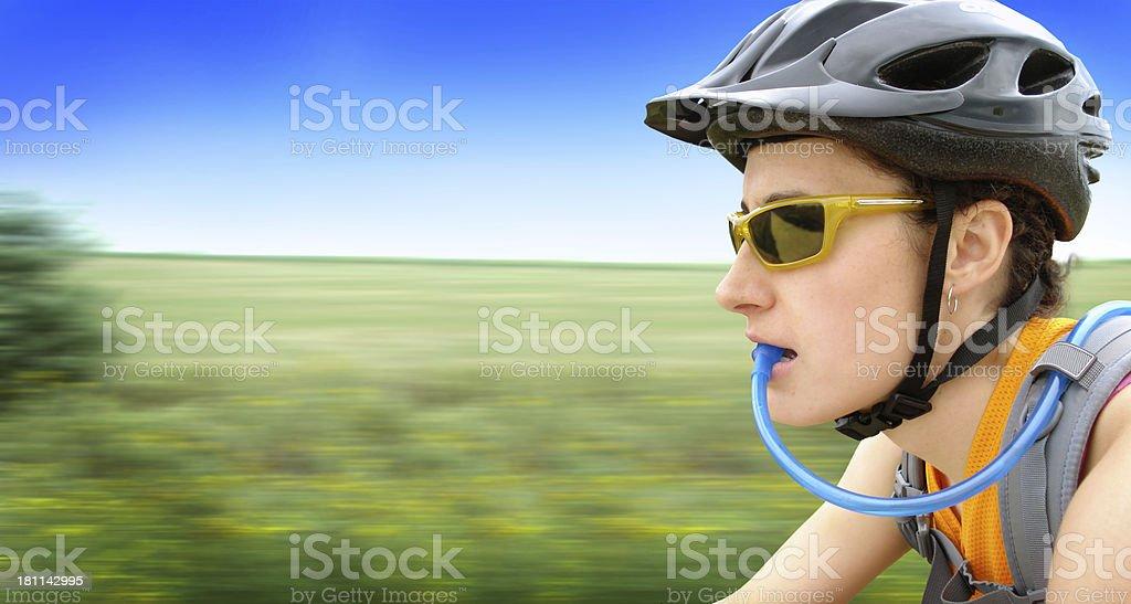 Jovem mulher com capacete de bicicleta e de água potável, Borrão de movimento foto de stock royalty-free