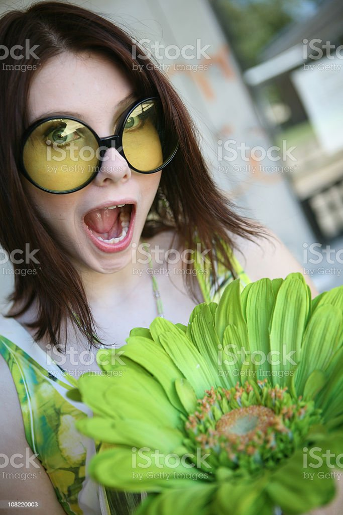 Young Woman Wearing Big Sunglasses Holding Giant Flower royalty-free stock photo