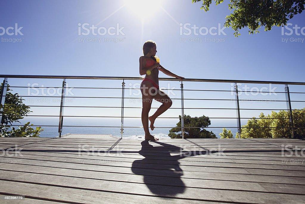 Young woman wearing bikini in balcony admiring the view stock photo