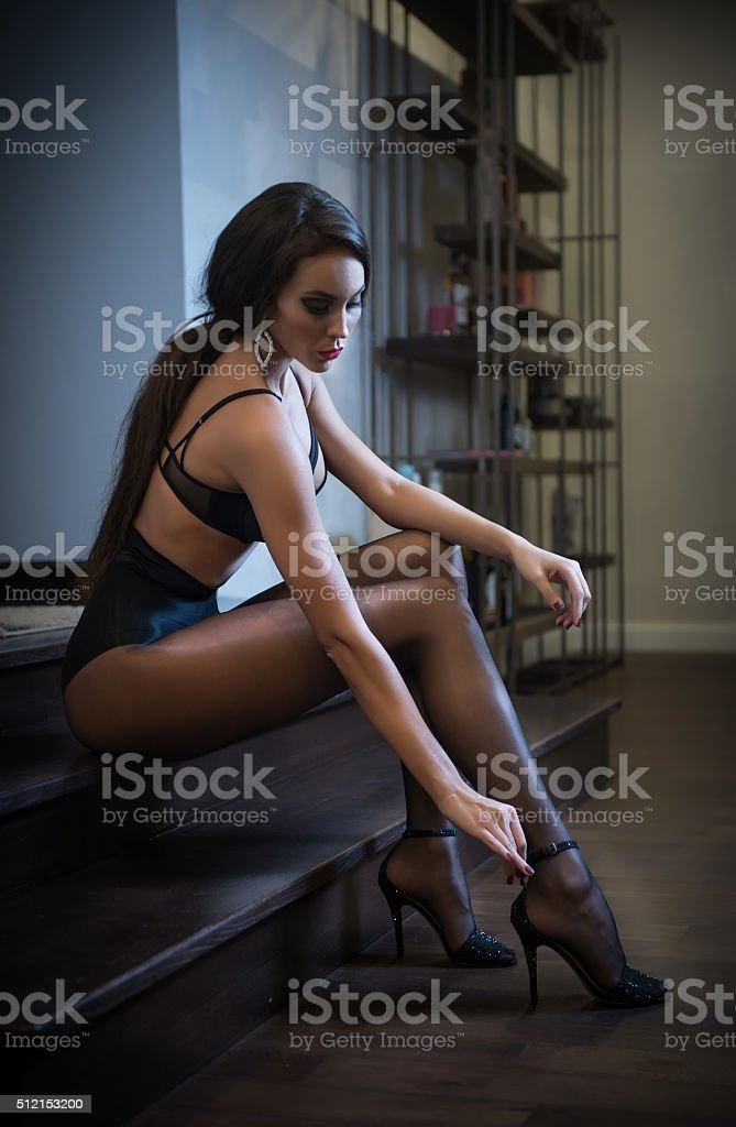 young woman wearing black lingerie sitting on bed stock photo
