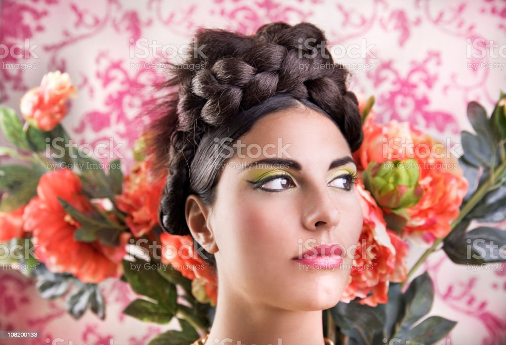 Young Woman Wearing Braided Bun Posing on Flower Background royalty-free stock photo