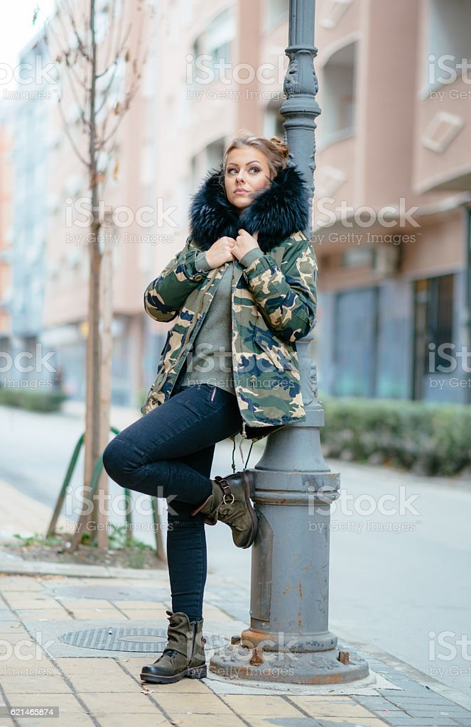 Young woman wearing camouflage military jacket with fur stock photo