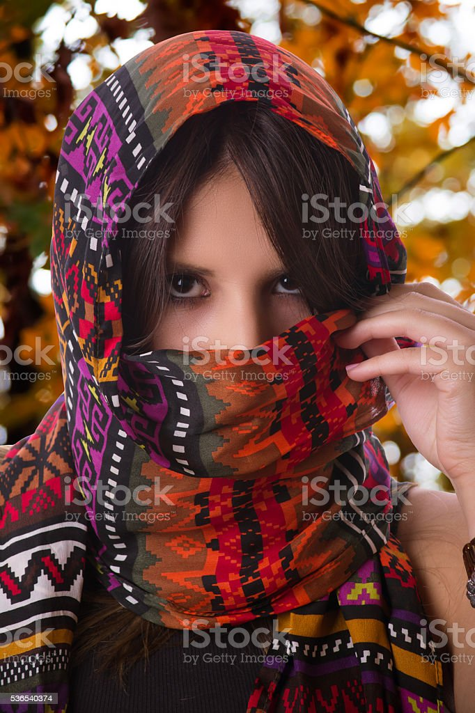 Young woman wearing colorful headscarf at autumn stock photo