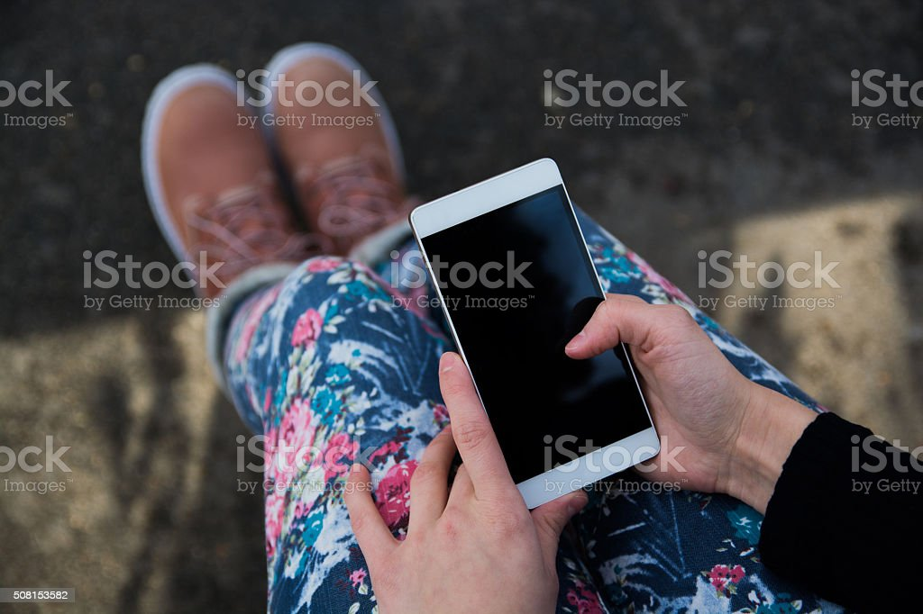 Young woman wearing colorful jeans and boots texting a message stock photo
