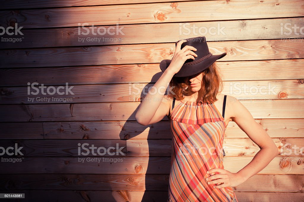 Young woman wearing cowboy hat by a cabin stock photo
