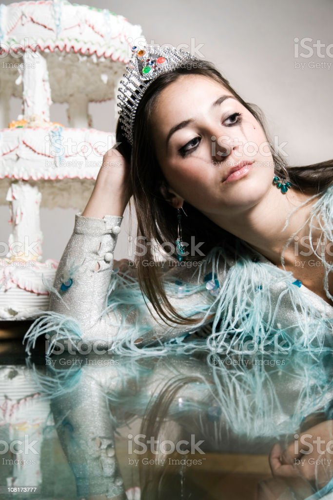 Young Woman Wearing Crown Crying Near Birthday Cake royalty-free stock photo