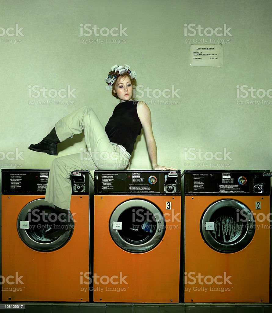 Young Woman Wearing Curlers in Hair Sitting on Laundry Machines royalty-free stock photo