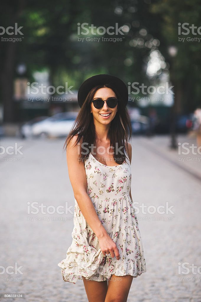 Young woman wearing dress and walking on the street stock photo