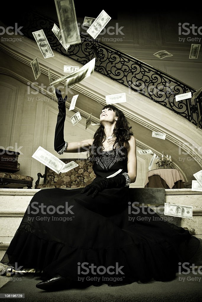 Young Woman Wearing Evening Gown Throwing Money in Air stock photo