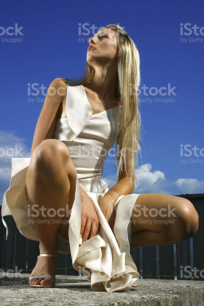 Young Woman Wearing Fashionable Dress and Posing Outside royalty-free stock photo
