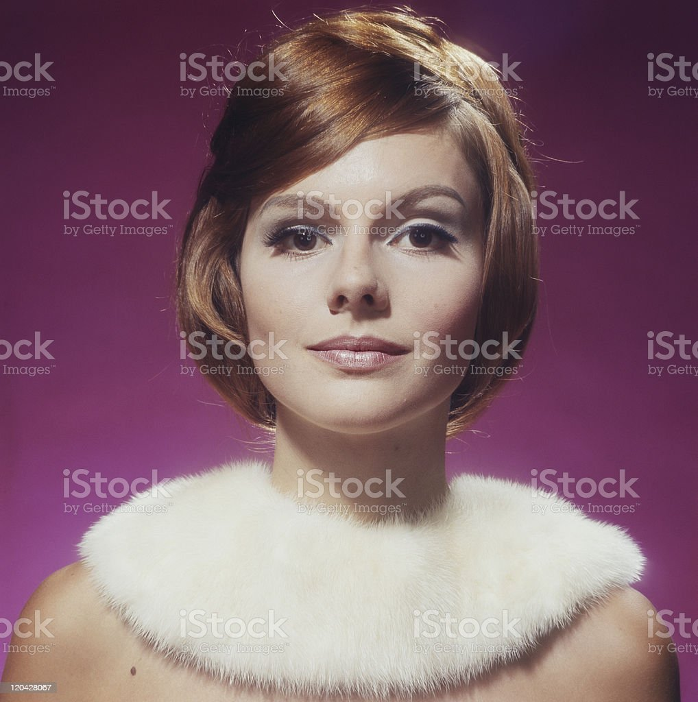 Young woman wearing fur against pink background, close-up, portrait stock photo