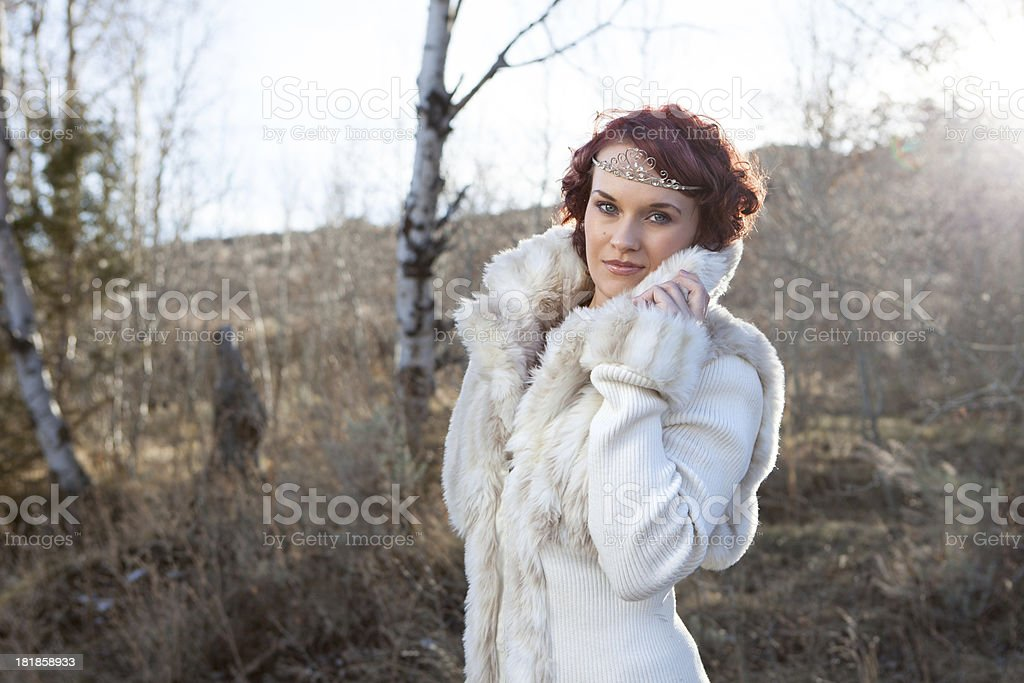 Young Woman Wearing Fur with Red Hair Backlit by Sun royalty-free stock photo