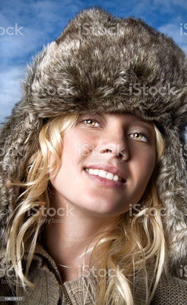 Young Woman Wearing Furry Winter Hat Outside Against Blue Sky royalty-free stock photo
