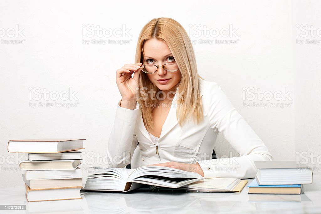 Young woman wearing glasses at table with books royalty-free stock photo